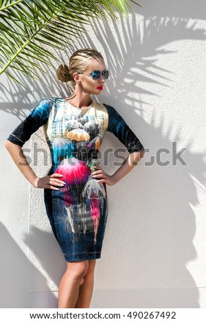 Beautiful phenomenal stunning  elegant luxury sexy blonde model woman wearing a dress and high heels and sunglasses stands on amazing view with palm tree shadow in Cannes, France