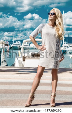 Beautiful phenomenal stunning elegant luxury sexy blonde model woman wearing a dress , high heels and sunglasses goes through the streets for shopping and in the background are yacht in Cannes,France