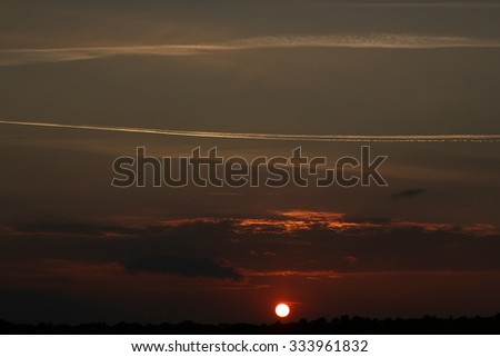 Beautiful phenomenon of nature sunset at countryside with fresh light trace of aircraft in sky orange clouds red sun in dark background, horizontal picture