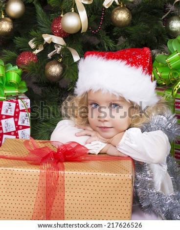 beautiful photo of cute little girl with blond curly hair  in Santa's hat sitting beside a decorated Christmas tree with big present - stock photo