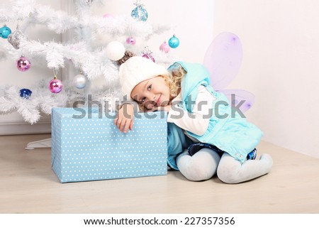 beautiful photo of cute little girl 5 years old with blond curly hair posing beside a Christmas tree at home - stock photo
