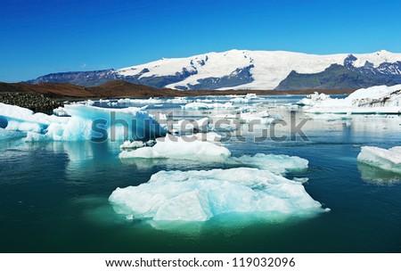Beautiful photo of Jokulsarlon Glacial lake full of floating icebergs - stock photo