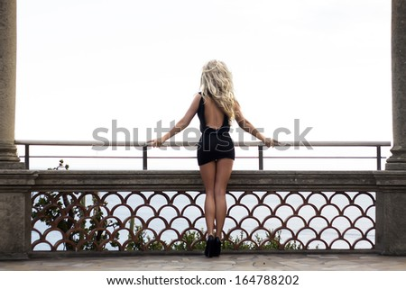 Beautiful photo of sexy blonde woman standing back. Girl with long curly hair. - stock photo