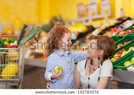 Beautiful photograph of a mother and daughter in the food department looking at each other and smiling. - stock photo
