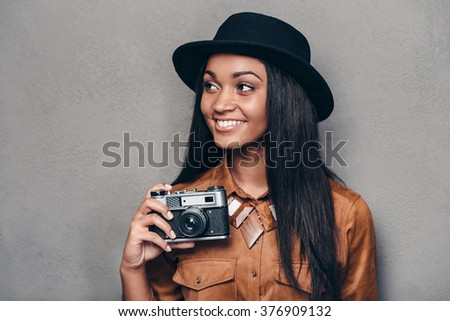 Beautiful photographer. Beautiful cheerful young African woman holding retro styled camera and looking away with smile while standing against grey background - stock photo