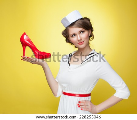 Beautiful pin-up girl dressed a sailor keeps the palm red shoes. Yellow background, close up - stock photo