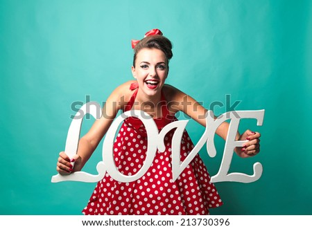 Beautiful pin-up girl holding LOVE word sign. Turquoise color background. - stock photo