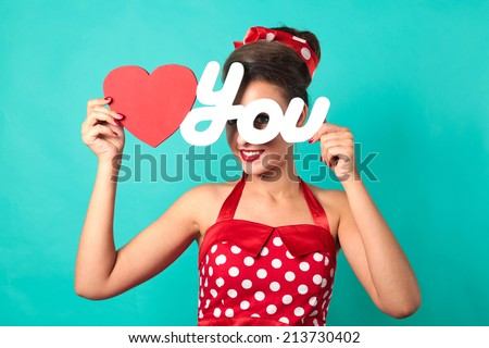 Beautiful pin-up girl holding LOVE YOU sign with red heart. Turquoise color background. - stock photo