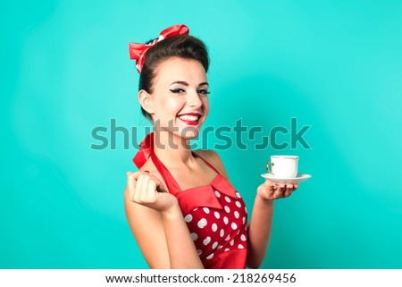 Beautiful pin-up girl holding small white tea cup. Turquoise color background. - stock photo