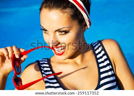 Beautiful pin up girl near the swimming pool. Summertime - stock photo
