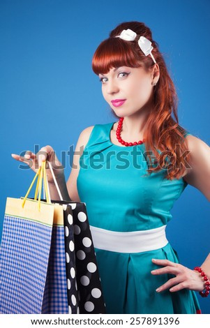 beautiful pin-up girl posing with shopping bags against blue background - stock photo