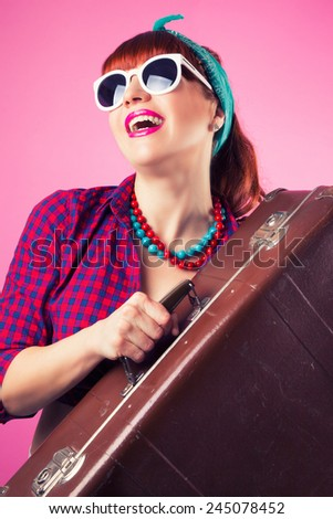 beautiful pin-up girl posing with vintage suitcase against pink background - stock photo