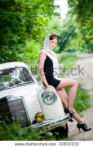 Beautiful pin-up styled girl sitting on retro car - stock photo