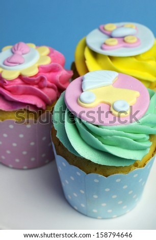 Beautiful pink, aqua blue and yellow cupcakes on white heart shape plate, for baby shower or children's party holiday and event. - stock photo