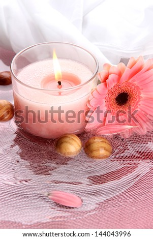 Beautiful pink candle with flower in water