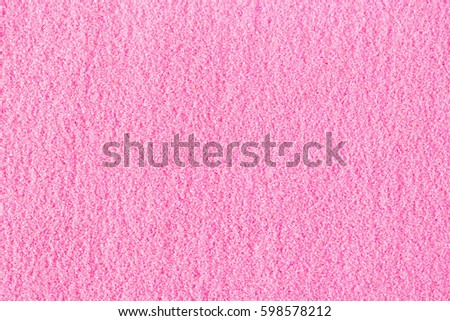 Beautiful pink decorative sand scattered on the table. Background of sand.