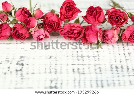 Beautiful pink dried roses on old wooden background - stock photo