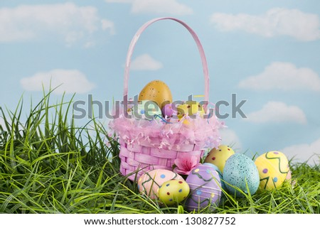 Beautiful pink Easter basket and ornate colorful eggs in green grass with blue sky behind