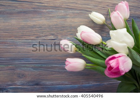 Beautiful pink flowers tulips on wooden table. Top view with copy space. Toned picture - stock photo