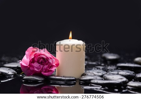 Beautiful pink rose with candle and therapy stones  - stock photo