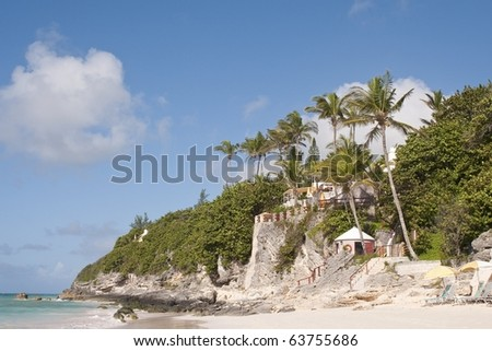 Beautiful Pink sand beaches with palm trees and cliffs in the background - stock photo