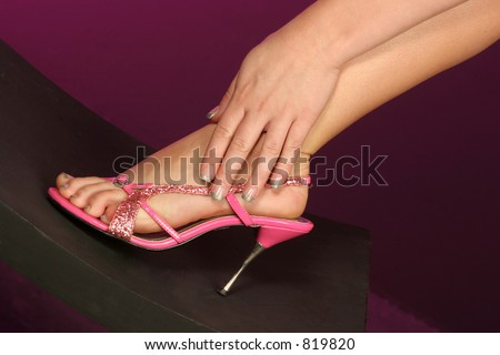 beautiful pink shoe on foot with hand wrapped at her ankle fingers well manicured - stock photo