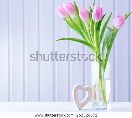 Beautiful pink tulips with decorative heart on wooden background - stock photo