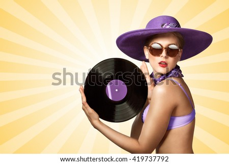 Beautiful pinup bikini model wearing sunglasses and hat, holding an LP microgroove vinyl record on colorful abstract cartoon style background. - stock photo