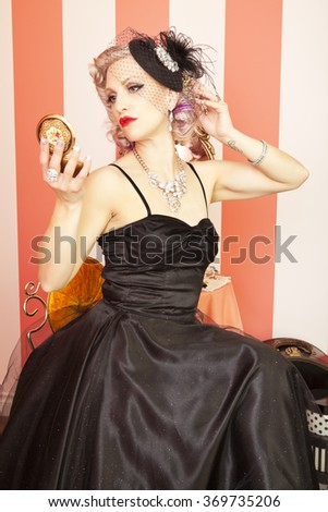 Beautiful pinup girl checking her hair in her compact mirror. - stock photo