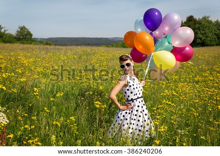 beautiful pinup girl with colorful balloon on a meadow