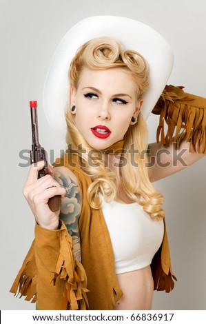 Beautiful pinup model dressed as Cowgirl - stock photo