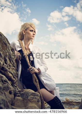 Beautiful pirate woman standing on the beach in boots and with nautical ropes in the hands.