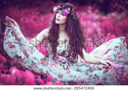 beautiful playful fairy  woman in fluttering floral dress in unreal pink field  - stock photo