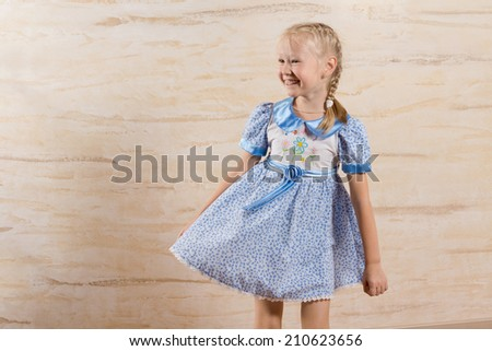 Beautiful playful little girl with a happy smile laughing as she twirls the skirt of her blue summer frock, with copyspace - stock photo