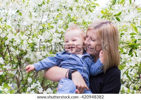 beautiful playful toddler boy with his young beautiful mother enjoying time together at the park at blooming springtime - stock photo