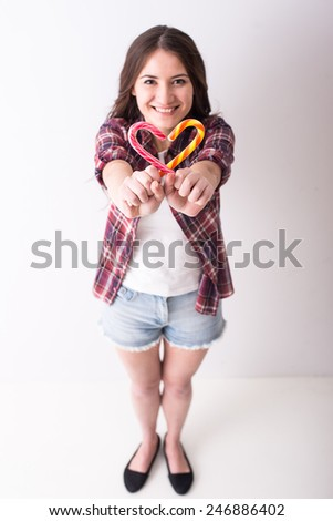Beautiful playful young girl with two colorful lollipops like heart on grey background.