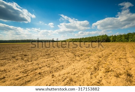 Beautiful plowed field under cloudy sky. Autumnal landscape of polish countryside.