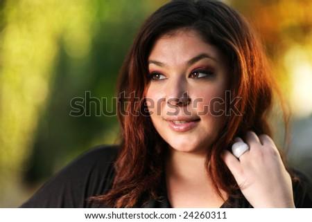 Beautiful plus size model outdoors. Shallow DOF. - stock photo