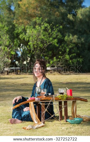 Beautiful polytheist woman in blue sitting outdoors