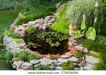 Beautiful pond in a backyard surrounded with stone during summer - stock photo
