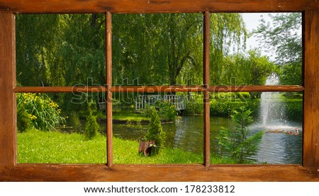 Beautiful pond in the summer, with  a cute lab puppy curiously watching some ducks swimming by, as seen through the cottage window. - stock photo