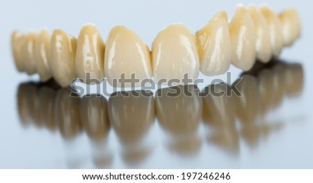 Beautiful porcelain teeth made by dental technician on mirror surface. - stock photo