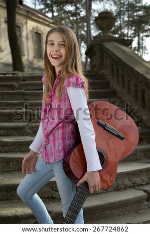 Beautiful Portrait of a Carefree Friendly Smiling Girl with Guitar in Her Hand Looking at the Camera, Three Quarter Length Shot - stock photo