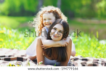 Beautiful portrait of a lovely beautiful mother and curly charming daughter outdoors , warm hugs, happy family sunny summer in park - stock photo