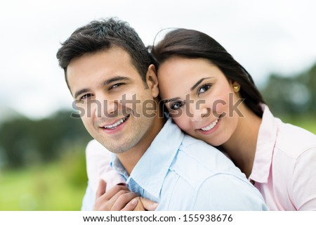 Beautiful portrait of a loving couple looking happy outdoors - stock photo