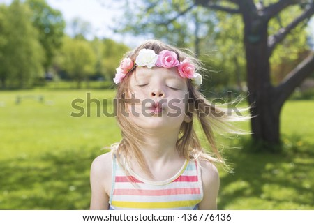 beautiful portrait of adorable blond young girl in preschool age wearing flowers in hairs and sending air kiss, on green lawn outdoors - stock photo