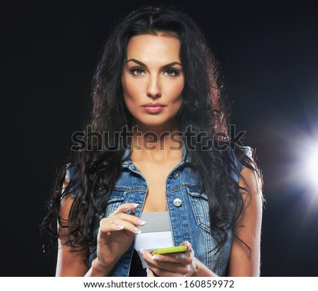 Beautiful portrait of european young woman model with mobile phone, on black background. - stock photo