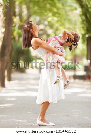 Beautiful portrait of little daughter playing with her mommy. - stock photo