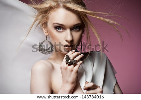 Beautiful portrait of sexy young haughty woman with precious ring and earrings closeup. Studio shot