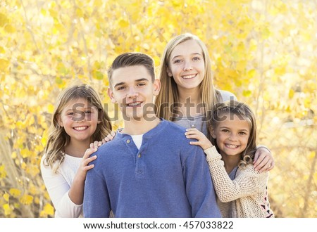 Beautiful Portrait of smiling happy kids outdoors. Four siblings standing together for a cute picture on a warm fall day - stock photo
